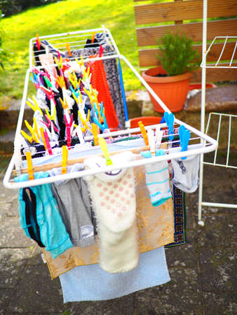 A vertical shot of the laundry on a hanging rack during daytime
