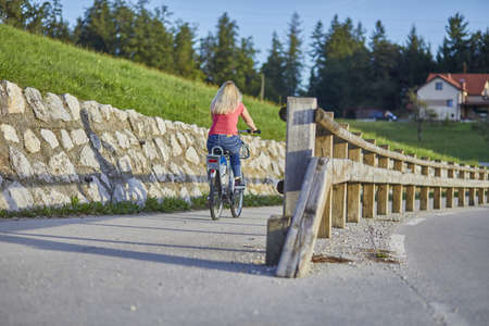 CELJE, SLOVENIA - Sep 10, 2019: Young woman driving, an electric bike on the bicycle pathway, uphill. 免版税图像