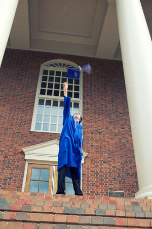 A vertical shot of a male in a blue mantle throwing his graduation cap up in the air