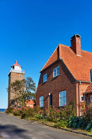 SVANEKE, DENMARK - Jun 28, 2019: Svaneke, Bornholm island, Denmark - June 28, 2019. Square-shaped Svaneke Lighthouse on the coast of Baltic Sea in Svaneke.