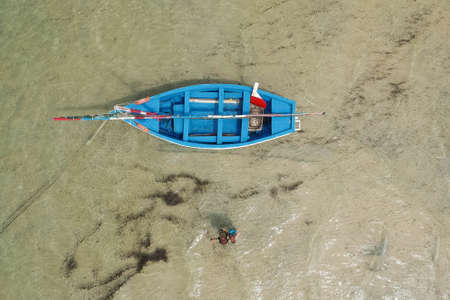 top view drone shot of couple next to a blue sailing boat in Bazaruto Archipelago, Mozambique