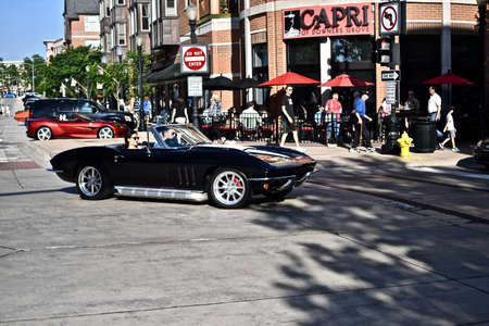 DOWNERS GROVE, UNITED STATES - Jun 07, 2019: A couple riding in a shiny black vintage car