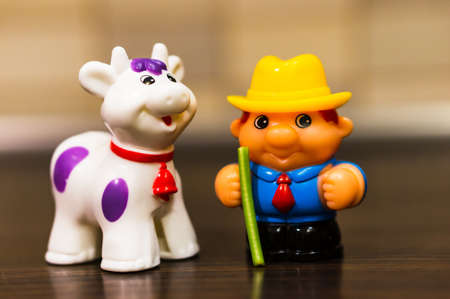POZNAN, POLAND - Jan 16, 2019: Plastic toy farmer and animal on a wooden surface.