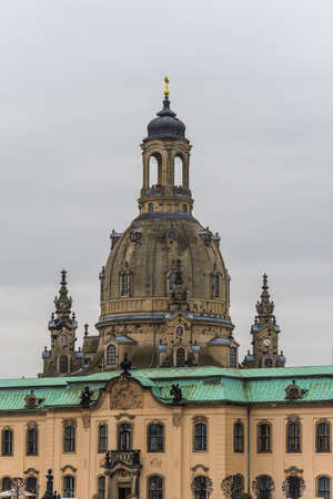 A vertical shot of the Frauenkirche Dresden with a cloudy sky in the background