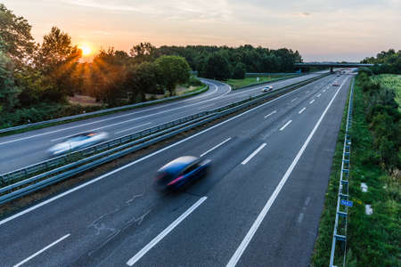 german highway at sunset with light trails from passing cars Stock Photo