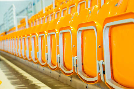 A closeup shot of yellow plastic seats in the stadium