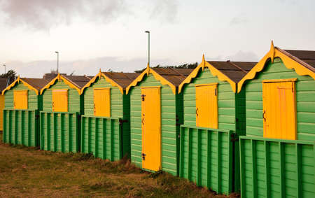 Small wooden green and yellow cottages in the rural area