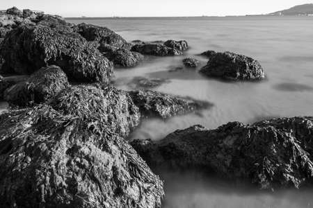 A black and white shot of the rocks and very blurry sea from the Sandsfoot beach in Dorset, UK