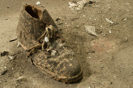 A closeup shot of an old worn out dirty boot on the ground Stockfoto