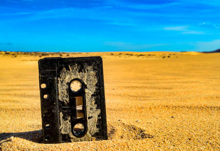 An old rusty music tape cassette in the sand in a desert 免版税图像