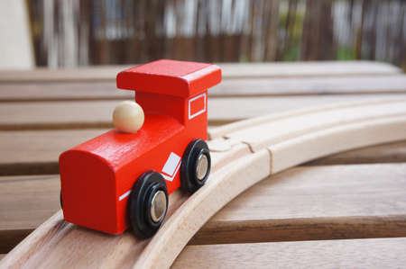A closeup shot of a red wooden toy  train on a wooden rail