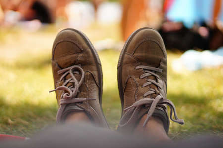 A soft focus shot of sock-less  feet in brown leather shoes resting on a park 写真素材