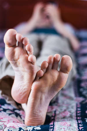 A vertical closeup shot of a male's feet while laying on the bed 免版税图像