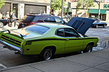 DOWNERS GROVE, UNITED STATES - Jun 07, 2019: A neon green vintage car parked at the side of the road with an open hood showing the car engine