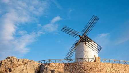 The Windmill of Campo de Criptana surrounded by rocks under the sunlight and a blue sky in Spain