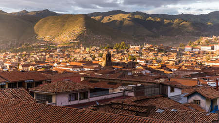 A beautiful shot of buildings with tiled roofs and mountains in the distance