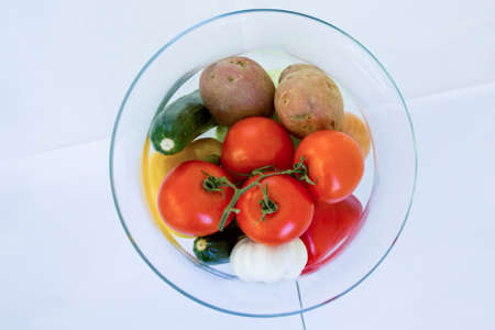 A high angle shot of a glass plate full of fresh vegetables with a white background