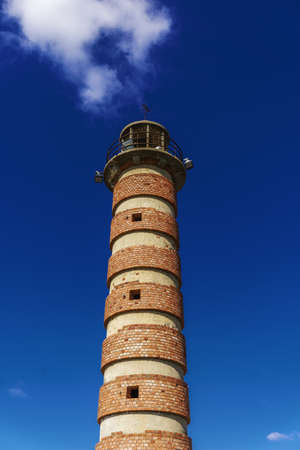 A low angle vertical of the lighthouse under a blue sky and sunlight in Belem 免版税图像