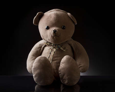 A cute brown childhood teddy bear with black color in the background