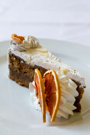 A vertical shot of a delicious slice of cake with white cream and dried lemon on the side