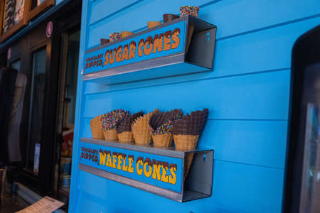 VERMONT, UNITED STATES - Jun 21, 2019: Ice cream shop showing an assortment of cones with blue walls. Both waffle cones and sugar cones are being displayed with various toppings