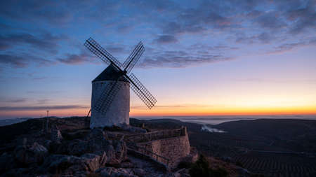 The Windmill of Campo de Criptana surrounded by hills during the sunset in the evening in Spain