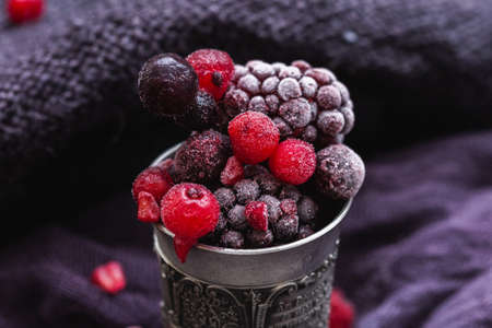 A beautiful shot of frozen berries in an antique silver cup on a purple background