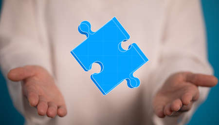 A blue piece of jigsaw puzzle over someone's hands