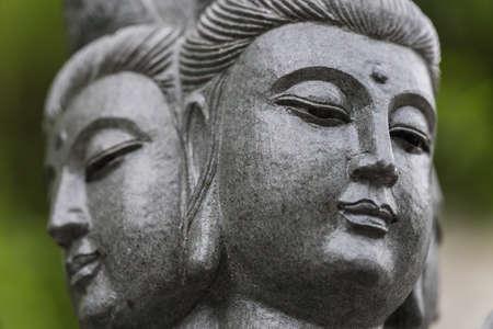 A closeup shot of a buddha statue with a blurred background