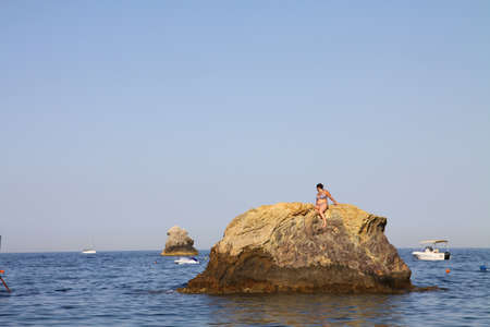 A female sitting on the rock in the sea in Messina, Italy