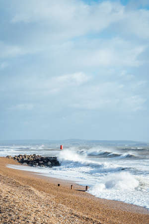 A vertical shot of waves washing the sandy beach during cloudy weather 스톡 콘텐츠