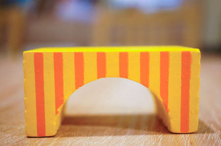 A closeup up of a yellow wooden arch block with orange stripes Banco de Imagens