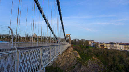 The Clifton Suspension Bridge surrounded by buildings and rocks covered in greenery under the sunlight