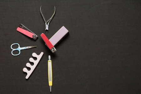 A high angle shot of a manicure set with a pitch-black background