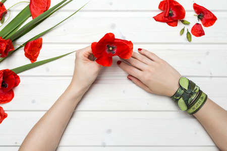 A high angle shot of a person with green bracelets holding a red poppy flower in a white wooden table