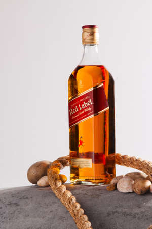 BIRMINGHAM, UNITED KINGDOM - Apr 24, 2019: A closeup shot of a bottle of whiskey tied with a tight rope on a white background