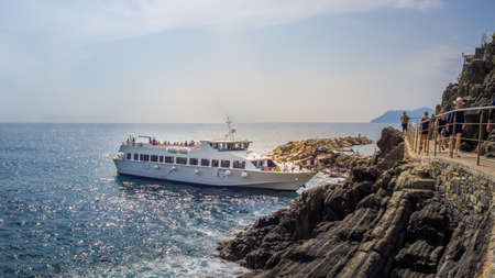 RIOMAGGIORE, ITALY - Jul 07, 2019: Tourists boat on the ocean overlooking Riomaggiore, Cinque Terre Editorial