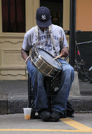 NEW ORLEANS, UNITED STATES - Sep 09, 2019: 09 September 2019 - New Orleans, United States: A street musician with a drum performs in the streets of New Orleans while smoking a cigarette.