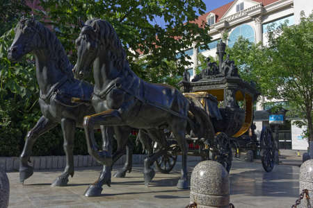 A wide angle shot of the statue of two horses carrying a chariot in a park surrounded by trees 新闻类图片