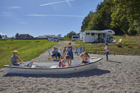 CELJE, SLOVENIA - Sep 10, 2019: Group of toddlers and their parents playing and enjoying on natural playground near the lake. 新闻类图片