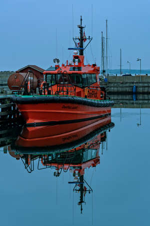 Motorboat moored in a small Baltic Sea port in Denmark 新聞圖片