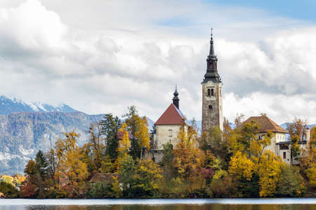 A historic castle surrounded by green trees near the lake under the white clouds in Bled, Slovenia 新闻类图片