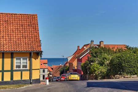 SVANEKE, DENMARK - Jun 28, 2019: Svaneke, Denmark - June 28, 2019. Cars parked on a steep street leading down to Baltic sea in Svaneke, Bornholm island, Denmark. 新聞圖片