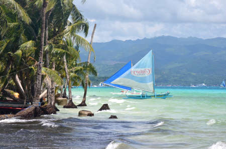 BORACAY, PHILIPPINES - Aug 09, 2010: sailing boat in rough sea with palm trees, Boracay, Philippines Editorial