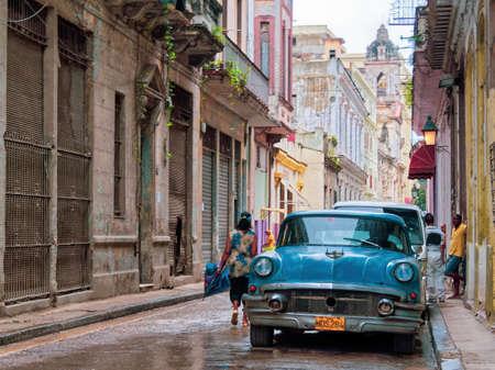 HAVANA VIEJA, CUBA - Jun 06, 2013: A wide shot of a blue car parked on the street near buildings and people in Havana Vieja, Cuba Redakční