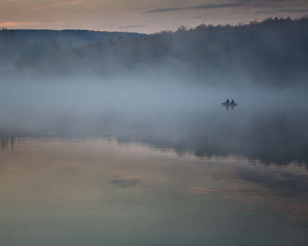 The silhouette of two fishermen on a boat at Spruce Knob Lake in the Monongahela National Forest in Randolph County, West Virginia