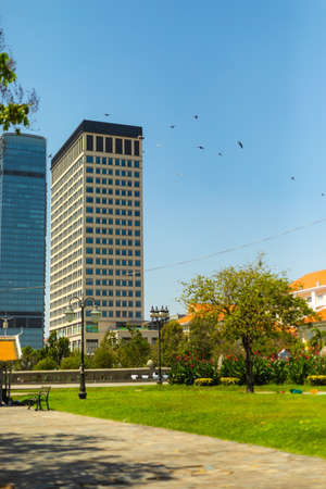 A vertical shot of a modern office building with a park in the foreground in Phnom Penh, Cambodia