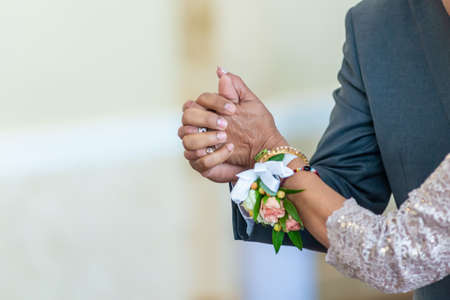 A closeup shot of a bride and a groom holding hands while dancing