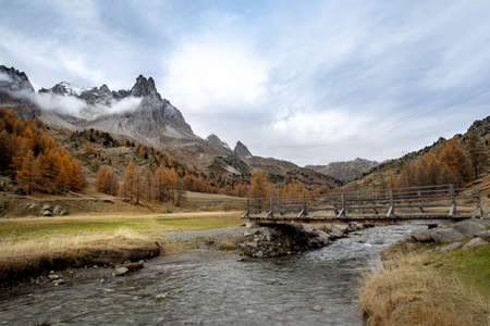 A river with an old bridge over it and mountains in the autumn