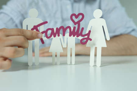 The white icons of people depicting a family and a man holding a purple family sticker
